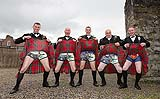 Groomsmen having fun showing what is under their kilts after the wedding on the grounds of King John's castle.