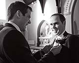 Groom putting button hole flower on groomsman on route to wedding reception at Ballygarry House in Tralee, Co. Kerry