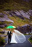 Couple braving taking on the weather on the Ring of Kerry on their wedding day.