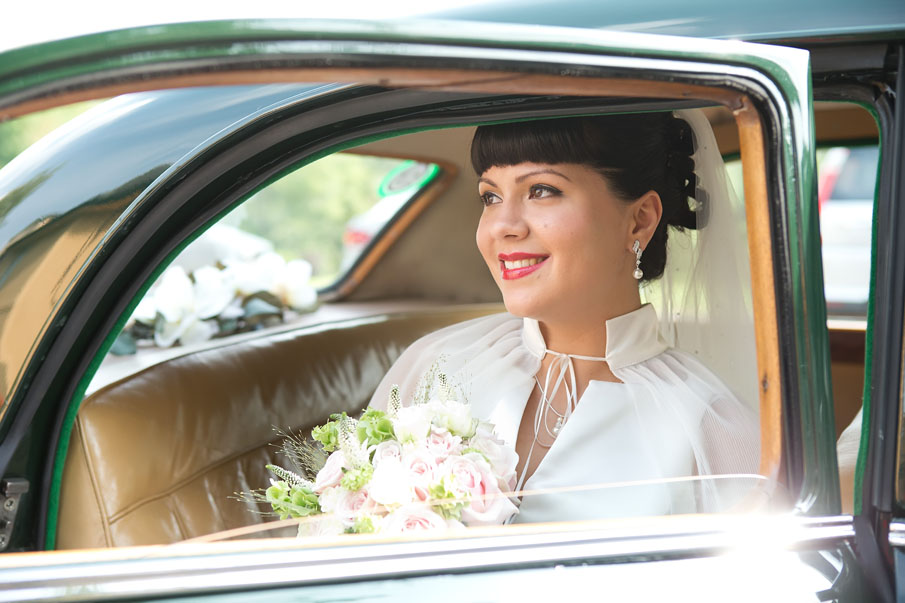 Bride in vidtage bridal car on her way to her wedding at the Mustard Seed, Ballingarry, Co. Limerick