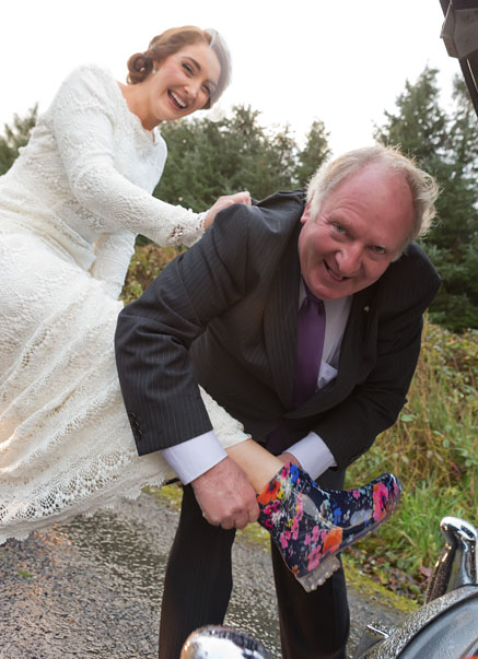 Chauffeur helps bride to put on colourful wellies on her way to BallyGarry House, Tralee, Co. Kerry.