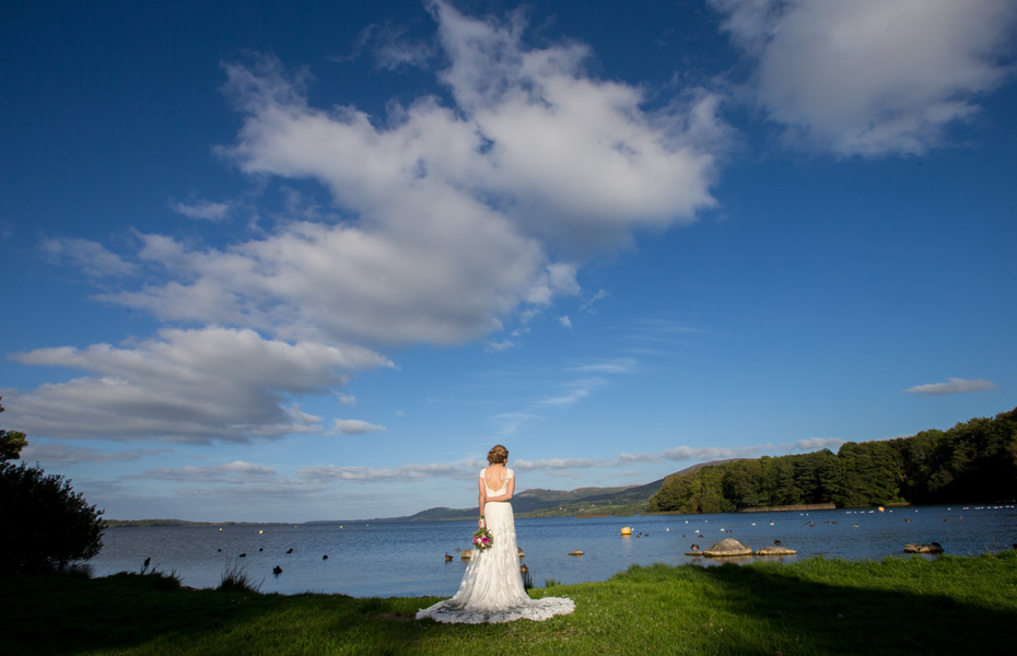 Bride taking a moment on her own to enjoy the fabulous view at a lake near Killaloe, Co. Clare, Ireland.