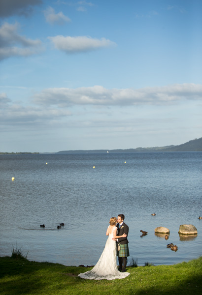 Wedding couple share a kiss after their wedding, at a lake near Killaloe, Co. Clare, Ireland.